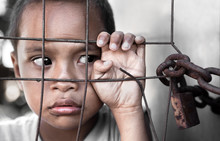 Boy Behind Fence In Asia Depicting Poverty - Focus On Hand