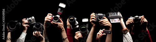 Photo Raised hands holding different photocameras