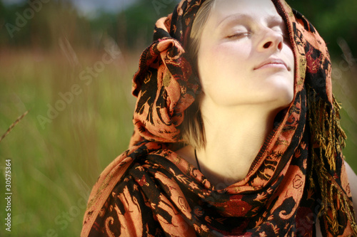 Photo sur Aluminium Gypsy woman with traditional kerchief over head sitting in meadow