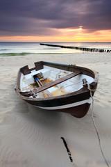 Fototapeta Morze Boat on beautiful beach in sunrise