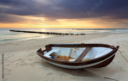 Fototapeta Boat on beautiful beach in sunrise obraz