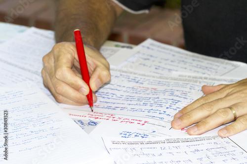 Foto  Professor korrigiert Prüfungsunterlagen