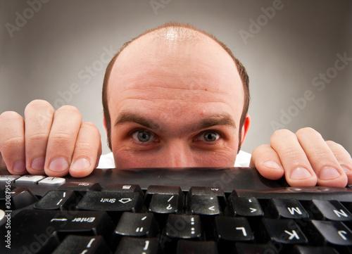 Photo  Timid nerd hiding under computer keyboard