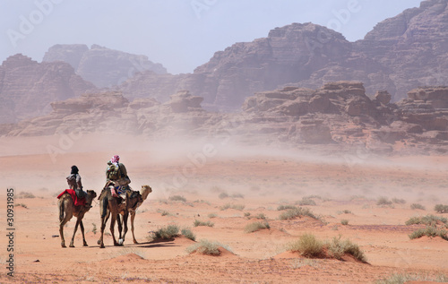 Photo  People on camels going through the desert storm