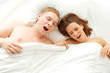 Yawn couple in their white bed
