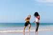 Sportliches Paar spielt Fangen am Strand