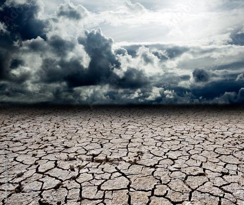 Платно paisaje con nubes de tormenta y suelo seco