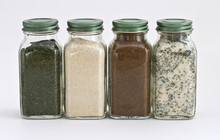 Set Of Four Spices In Glass Jars With White Background