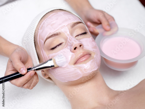 Fotografía  Girl receiving cosmetic pink facial mask