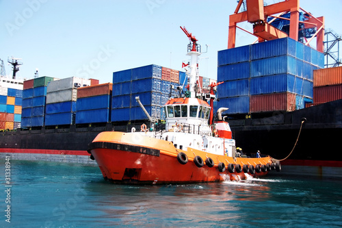 Tug boat pulling out container ship