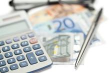 Money, Pen, Glasses And Angled Pocket Calculator