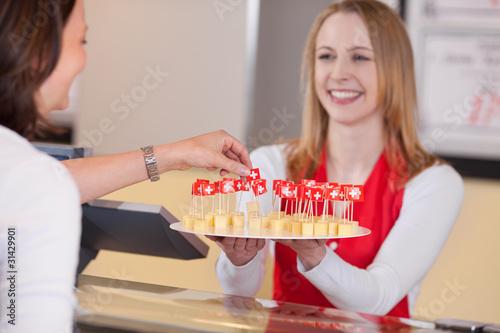 Fotografía  freundliche verkäuferin bietet käse zum probieren an