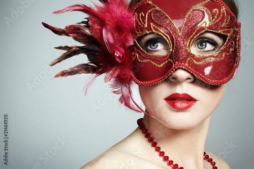Fotografie, Obraz  The beautiful young woman in a red mysterious venetian mask