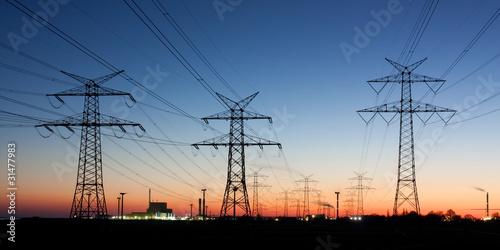 фотография  Strommasten in der Abenddämmerung, am Horizont Kernkraftwerk