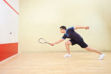 Squash Player Hitting A Ball I...