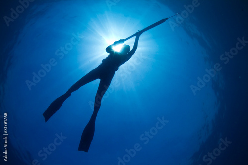 Photo A silhouette of a young woman spearfishing