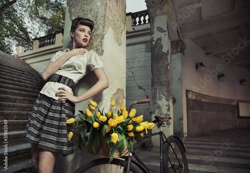 Obraz Piękna brunetka pozuje przy rowerze z żółtymi tulipanami - fototapety do salonu