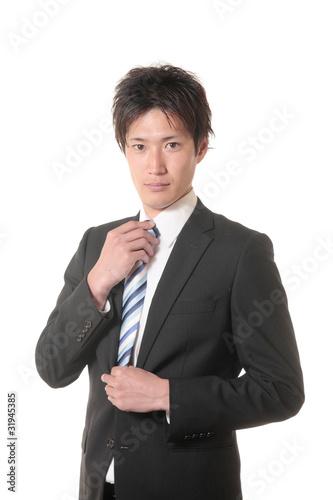 ネクタイを締めるスーツの男性