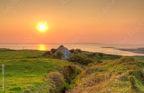 Naklejki krajobraz irlandzki-domek-letniskowy-w-poblizu-oceanu-o-zachodzie-slonca