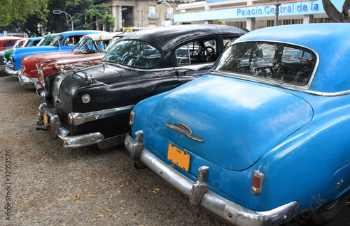 Photo Stands Old cars Vintage Cars Parked in a street of Havana, Cuba