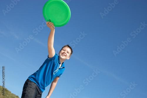 Valokuva  Boy playing frisbee on beach