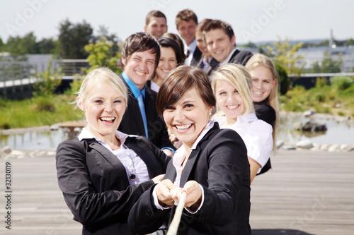 Fotografie, Obraz  Lachende motivierte Mitarbeiter ziehen am Seil