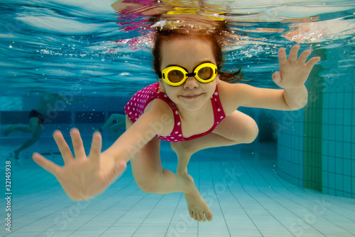Fotografía  The girl smiles, swimming under water in the pool