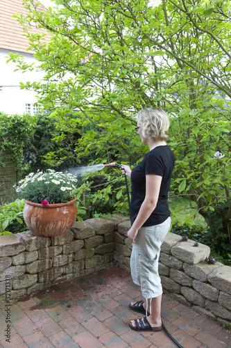 Fotobehang Tuin Hausfrau beim Blumen wässern