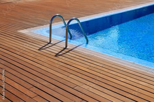 Fotografia blue swimming pool with teak wood flooring