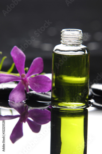 Poster Spa massage oil a black stones with pink orchid reflection