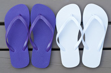 Two Pairs Of Flip Flops On A Deck