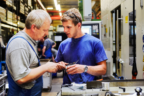 Fotografía  skilled workers controlling a workpiece