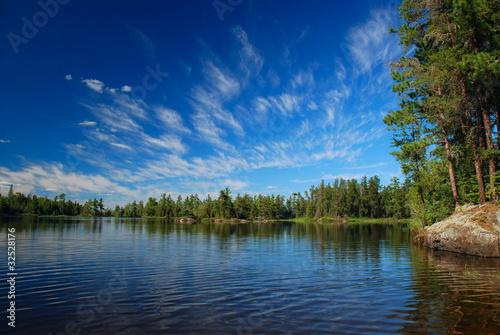 Fotobehang Meer / Vijver A wilderness lake and summer skies