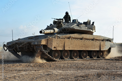 Man in field with tank and weapons Fototapeta