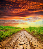 cracked rural road in green grass and cloudy sky - 32586717