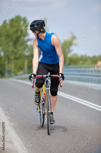 Poster Cycling Professional biker riding on race bike looking behind