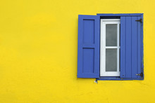 Colorful Yellow House With Blue Shutters In Governor's Harbour