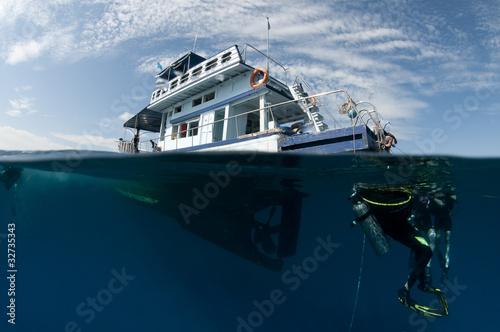 Fototapeta boat and scuba divers over under shot,half underwater obraz