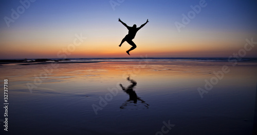 Obraz Silhouette of a jumping man on the beach by the ocean - fototapety do salonu