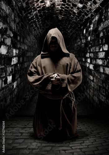 Praying monk in dark temple corridor Fototapet