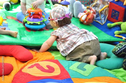 Fotografie, Obraz  bébé fille qui joue sur son tapis d'éveil d'activité