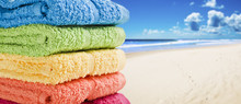 Colorful Towels On A White Beach