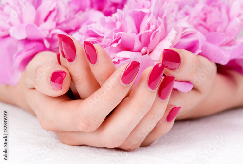 Staande foto Manicure Woman cupped hands with manicure holding a pink flower