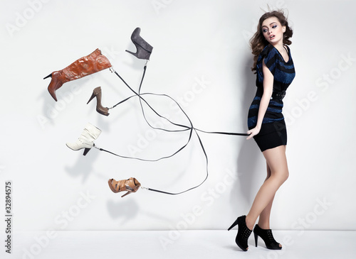 Fotografia  Young woman with many shoes