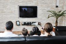 Family Wathching Flat Tv At Mo...