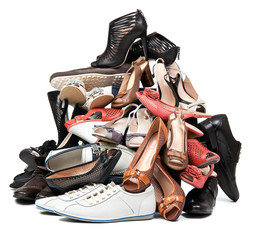 Pile of various female and male shoes over white