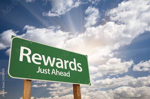 Fotografía  Rewards Green Road Sign Against Clouds