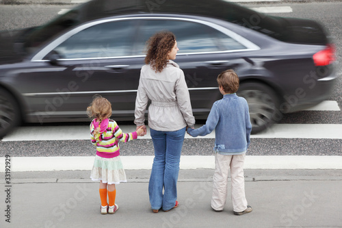 Fotografia, Obraz  mother holds hand of daughter and son and standing near road