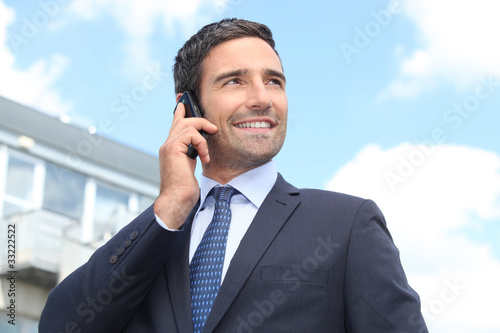 Fotografía  Property salesman stood outdoors with mobile telephone