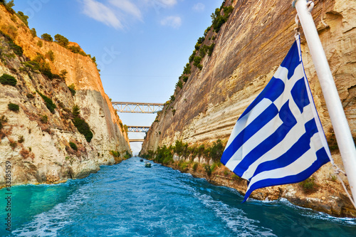 Leinwand Poster Corinth channel in Greece and greek flag on ship